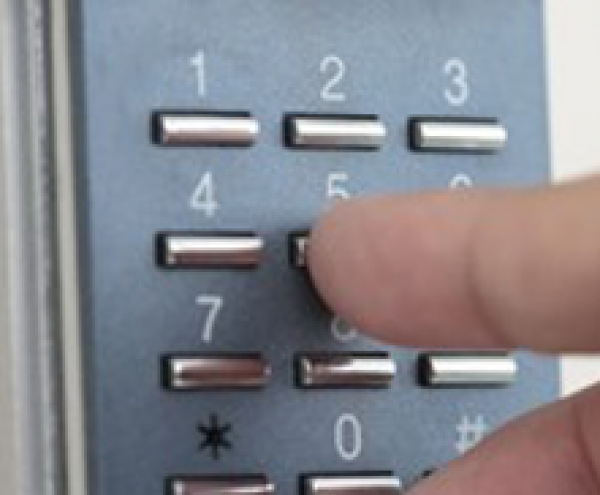 Person using a code pad to open a door with access control system