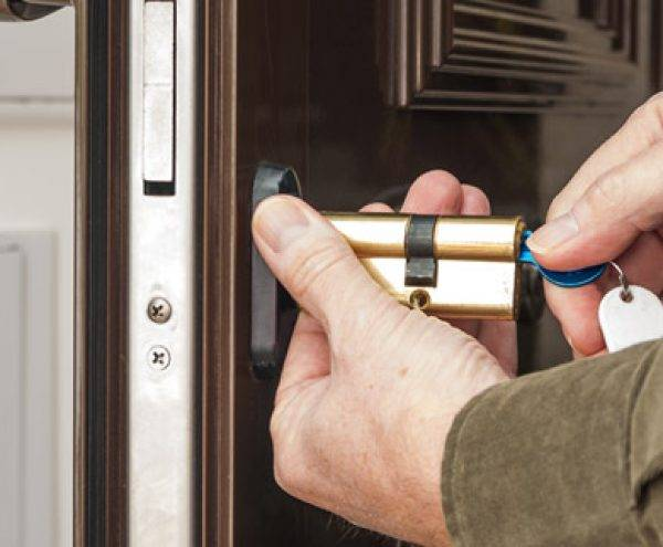 Locksmith services expert installs new lock cylinder on door