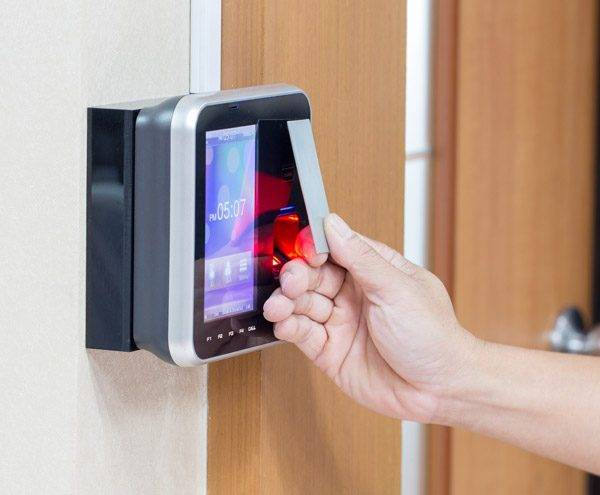 Staff member uses door entry system with proximity reader card