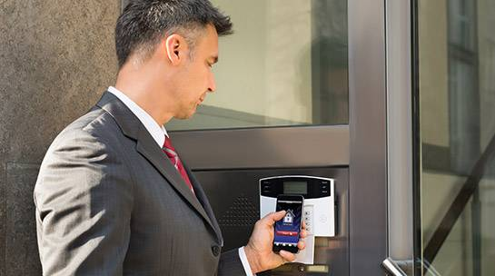 Staff member uses door entry system with mobile device to enter office building