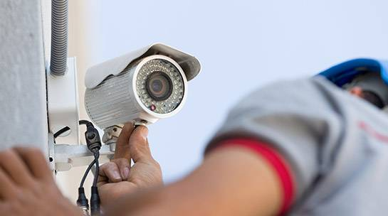 Engineer installs CCTV security system outside office building