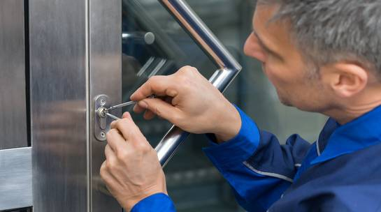 Locksmith services expert fixing lock cylinder in office building main entrance door